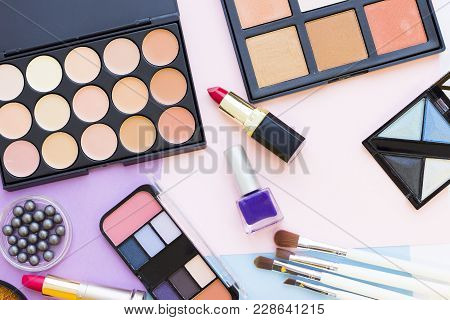 Face Foundation, Concealer, Smokey And Beige Eyeshadow Palettes, Lipstick And Brushes On A Pastel Pi