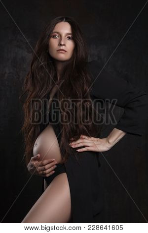 Studio Photoshoot Of Pregnant Female On Dark Background In Black Clothes