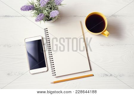 White Wooden Office Desk With Notepad, Pencil, Telephone, Cup With Coffee And Flower