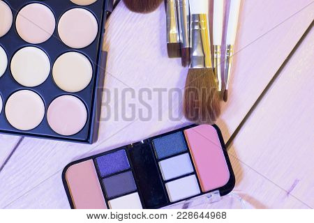 Palettes Of Concealer, Foundation And Eyeshadow And A Set Of Brushes On White Wooden Background, Top