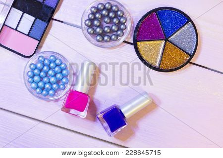 A Palette Of Eyeshadow, Colorful Glitter, Grey And Blue Pearl Eyeshadow In Balls And Nail Polish On