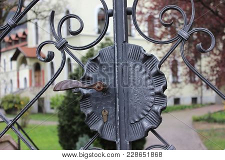 Closed Metal Garden Gate. Vintage Garden Gate With Door Handle Closed. Old Gate With Garden And Hous