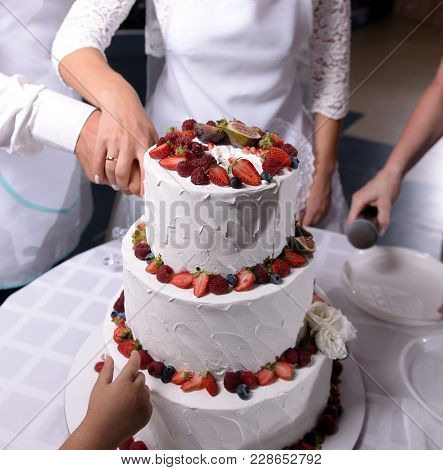 Close Up Delicious Wedding Cake Being Cut By Newly Married Couple