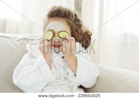Child In Bath Robe With Cucumber Slices On Eyes And Facial Mask On Face