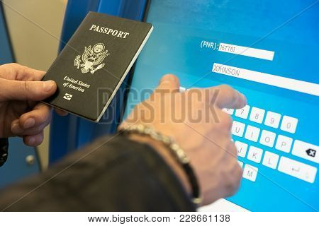 A Man With A Us Passport And Boarding Pass Fills The Electronic Form Of Self-registration On The Fli