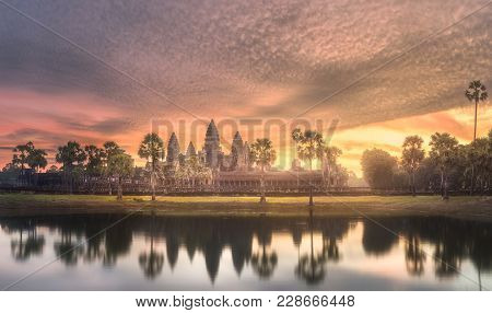 Sunrise View Of Popular Tourist Attraction Ancient Temple Complex Angkor Wat With Reflected In Lake