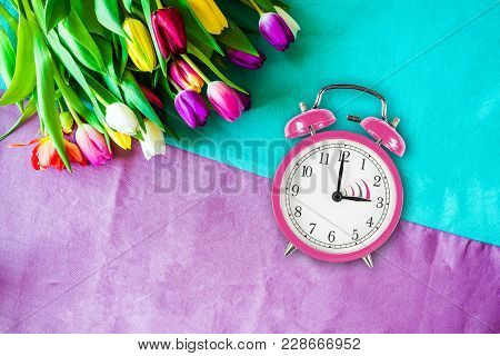 Change To Daylight Saving Time Photo Of Pink Alarm Clock From Above As Flatlay With A Bunch Of Tulip