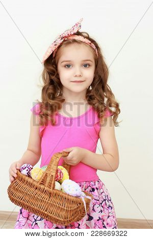 Portrait Of Little Girl Holding Easter Basket Of Painted Eggs. Portrait Of Easter Little Girl Holdin