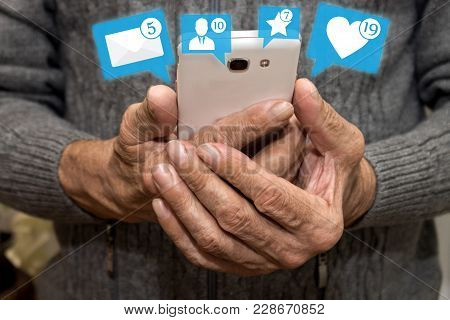 Elderly Man Holding Smartphone With Icons Of Notifications From Social Media. Social Media For The E