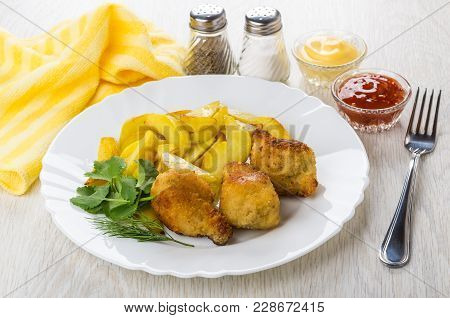 Fried Chicken Winglets In Breading With Potato In Plate, Bowls With Sauces, Pepper, Salt, Fork On Wo