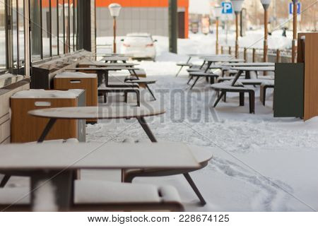Summer Café In The Winter.tables And Benches Are Covered With Snow