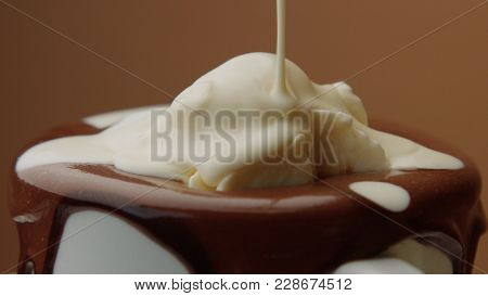 Cup Of Hot Chocolate With A Cream And Liquid White Chocolate Pouring On It. Closeup