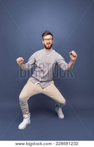 Handsome Young Bearded Man In Glasses Dancing In Studio. Hands Up.