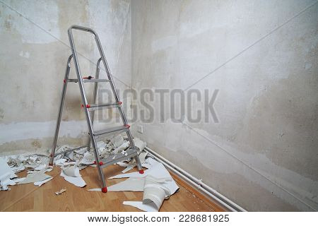 Empty Room With Bare Walls, Ladder And Old Wallpaper Scraps On Floor During Redecoration, Diy Home I