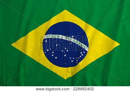 Brazil Flag Blowing In The Wind. Fabric Texture Of The Flag Of Brazil.