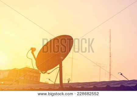 Silhouette Of Satellite Dish Antenna On Top Of The House