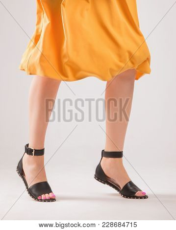 A Girl In A Yellow Soaring Skirt And Black Fashionable Sandals