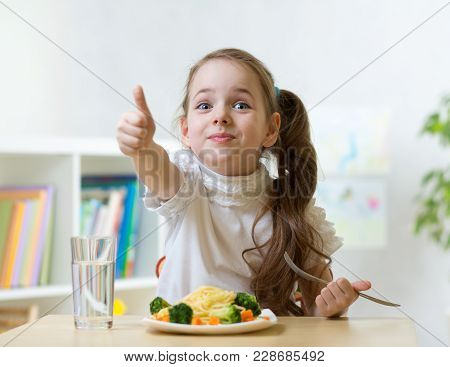 Smiling Child Girl Eats Healthy Food Showing Thumb Up