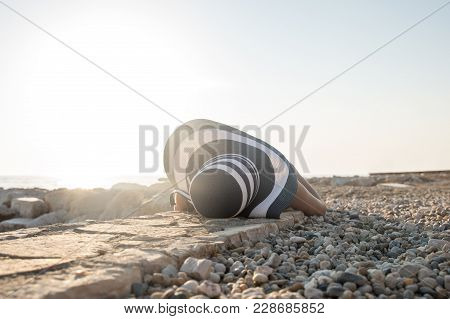 Woman In A Sunhat Relaxing On A Stony Beach Lying On Her Back Sunbathing In A Head To Toe View Of Th