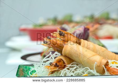 Fried Shrimps Wrapped And Crispy Fried Noodles With Row Of Various Vietnamese Food As Background Wit