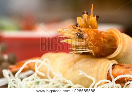 Close Up Of Fried Shrimps Wrapped And Crispy Fried Noodles With Various Food As Background With Warm