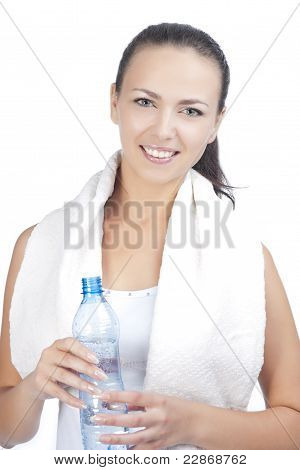 Portrait Of Young Woman Standing With Bottle Of Pure Water Having Towel Around Neck