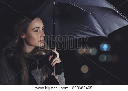 Portrait of a beautiful authentic woman standing with an umbrella on rainy night, conceptual photo of loneliness and sadness