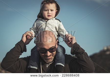 Child is sitting on his father's shoulders, handsome dad playing with his cute little son, enjoying parenthood, family love concept