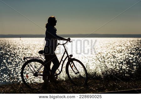 Woman relaxing with bike at seaside