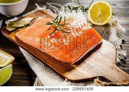 Fresh raw salmon fillet on cutting board on wooden background