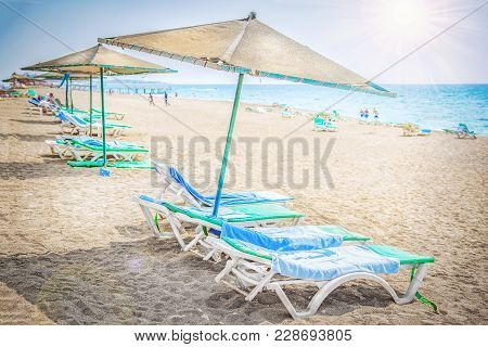 Tropical Resort Sea Beach. Umbrellas And Chaise Lounges Near Sea On Sandy Beach. Relax And Rest On B