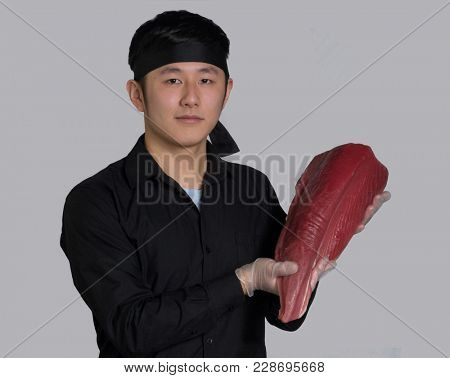 Asian cook hold a crude tuna fish fillet portrait.