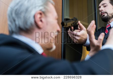 Criminal threatening a businessman in the office