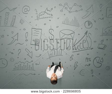Young contemplating businessman stands in front of business graphics