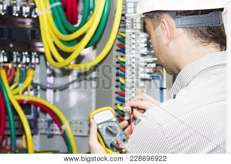 Engineer Makes Measurements With Multimeter In Electrical Cabinet. Electrician With Tester In The Ha