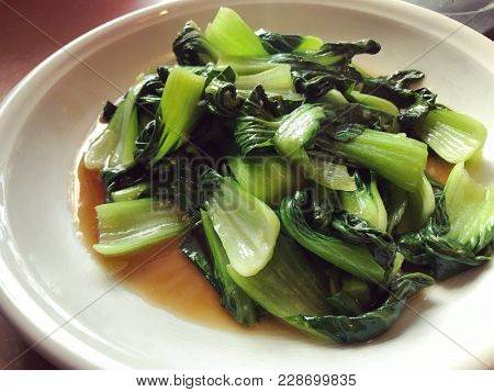 Stir fried nai bai chinese greens in oyster sauce and garlic on white plate.