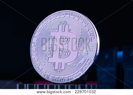 Close-up of bitcoin and processor on pink background