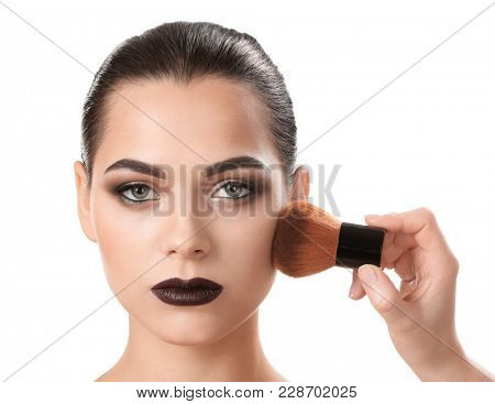 Professional visage artist applying makeup on woman's face against white background