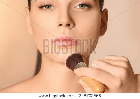 Professional visage artist applying makeup on woman's face against light background
