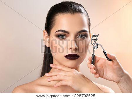 Professional visage artist curling woman's eyelashes against light background