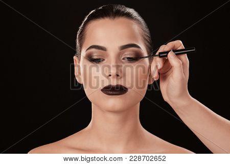 Professional visage artist applying makeup on woman's face against black background