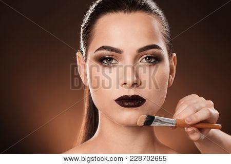Professional visage artist applying makeup on woman's face against dark background