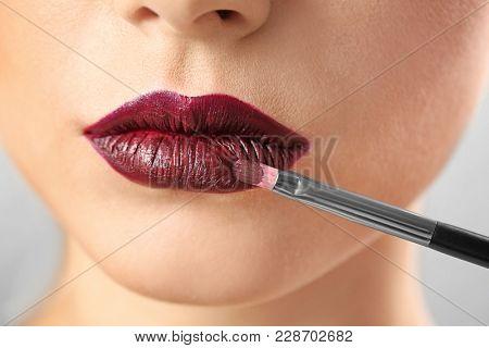 Woman applying makeup, closeup. Professional visage artist work