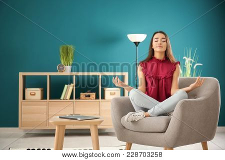Beautiful young woman meditating while sitting in comfortable armchair at home
