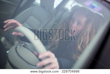 Pretty young woman driving her new car (shallow DOF; color toned image)