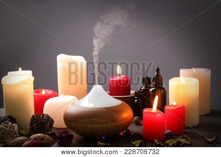 Aroma lamp and candles on table