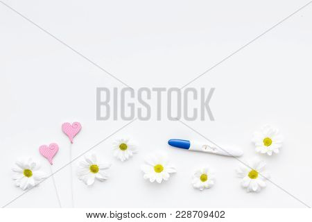 Joy Of Long-awaited Pregnancy. Pregnancy Test With Two Stripes Near Flowers On White Background Top