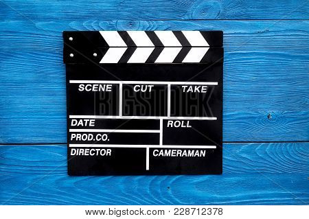 Film Concept. Clapperboard On Blue Wooden Background Top View.