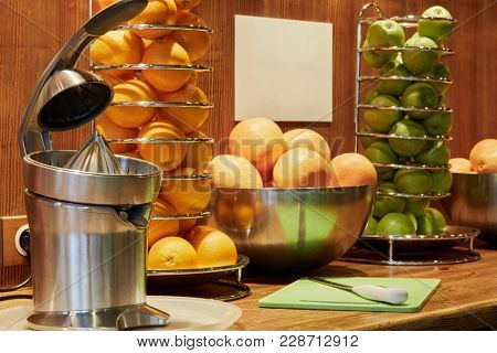 Electrical juicer, spiral holders and bowls with oranges and apples on wooden bar counter.