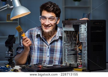 Computer repair man cleaning dust with brush